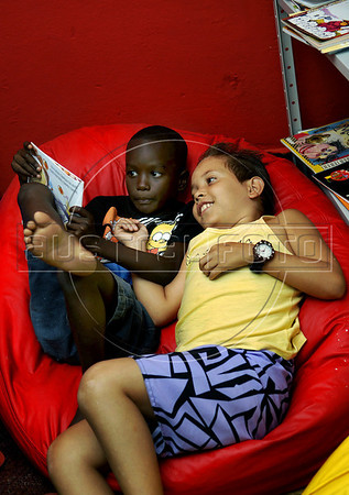 """Criancas leem na biblioteca dirigida por Otavio Cesar Junior """"O livreiro do Alemao"""", fundador do projeto """"Ler  é Dez – Viva Favela!"""" no Complexo do Alemao, Rio de Janeiro, Brazil, junho 24, 2011. (Austral Foto/Renzo Gostoli)"""