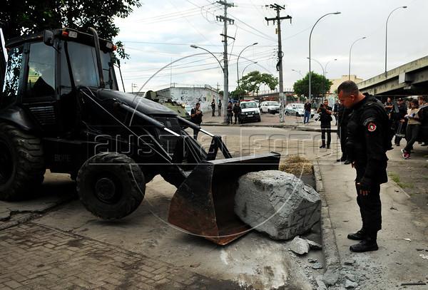 FAVELA DO CAJU - Um trator da Policia Militar retira obstaculos colocados para impedir a passagem de veiculos durante a ocupaçao do complexo de favelas do Caju, Rio de Janeiro, Brasil, Março 3, 2013.   (Austral Foto/Renzo Gostoli)