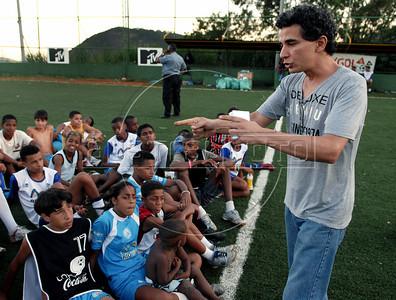 FUTEBOL NA FAVELA DOS PRAZERES -   Charles Siqueira, coordenador, fala com criancas do projeto Premier Skill-Esporte Seguro na favela pacificada Dos Pazeres, Rio de Janeiro, Brasil, Dezembro 22, 2011.  (Austral Foto/Renzo Gostoli)