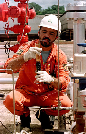 A worker for Petrobras checks crude oil at the Urucu oil well in the Amazon.(Douglas Engle/Australfoto)