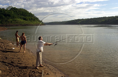 People fish on the banks of the Parana River downstream from the massive Itaipu Hydroelectric station and near where the Iguacu River flows into it, in Foz do Iguacu, Brazil. The meeting of the Iguaçu and the Parana, considered second in size only to the Amazon River among South American rivers forms the Brazilian borders with Argentina, upper left, and Paraguay, upper right.(Douglas Engle/Australfoto)