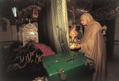 Praying for her own private miracle, a devotee will kiss the grave of Kabiruddin Daula Shah and drop a silver offering into the green box.