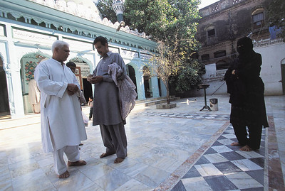 """Those who come to pray for favors must donate to the upkeep of the shrine.  Previously the donations went directly to Mr. Shah, but now they go to a government department responsible for the maintenance of shrines. Shah's family run the shops around the shrine and """"supervise' the rat children. Gujrat, Pakistan."""