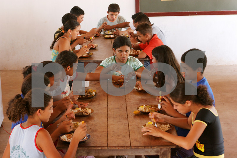 Students eat lunch prepared with food they helped grow organically at the Escola Familia Agricola Antonio Fontenele (EFA) near Lago do Junco in Brazil's northeastern state of Maranhao. Students, many who come from far away, alternate living at the school and at home in 14 day periods. The school is supported by the Association of Land Reform Settlements of Maranhao State (ASSEMA), an umbrella NGO of associations operated for and by rural peasants and babau nut crackers. Founded in the late 1980s as a result of land conflicts in the region, It's main goal is to improve living conditions in the countryside by promoting local and family oriented agricultural production, while using and preserving the babassu palm trees. British NGO Action Aid has helped support ASSEMA since 1999 - in particular the Escola Familia Agricola Antonio Fontenele (EFA). (AustralFoto/Douglas Engle)