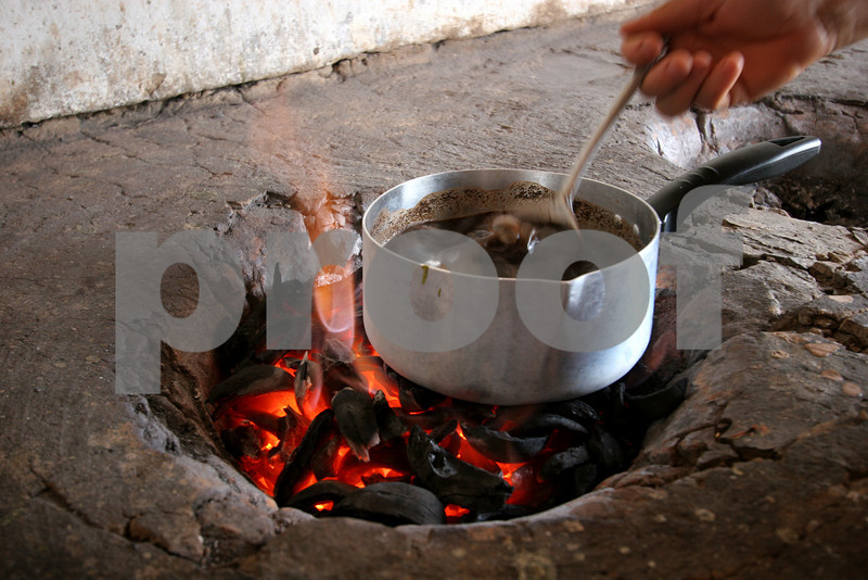 A woman makes coffee on a fire fueled by babassu nut shells in the countryside of Brazil's northeastern state of Maranhao.  The babassu palm, native to this northeastern corner of Brazil, is an important part of the local culture and economy - more than 60 products come from it including oil used for cooking and cosmetics as well as the nutshell which is used as cooking fuel. The Association of Land Reform Settlements of Maranhao State (ASSEMA) is an umbrella NGO of associations operated for and by rural peasants and babassu nut crackers, which British NGO Action Aid has helped support ASSEMA since 1999. (AustralFoto/Douglas Engle)