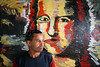 Hercules Miranda stands near a panel with a painted copy of the Mona Lisa in an abandoned building in central Sao Paulo, Brazil, Jan. 18, 2006. Hercules is one of thousands of squatting residents of a 22 floor abandoned building commonly referred to as the Prestes Maia occupation, after the avenue it is on in central Sao Paulo. The squatters are part of the Brazil's sem teto or 'roofless' movement - an urban coalition that is gathering steam in cities across the country. The movement is the urban equivalent to the better-known  MST, Brazil's Movimento dos Sem Terra or Landless Movement which has spearheaded the campaign for land reform since the 1980s. The MST defends Brazil's impoverished rural workers and reclaims unproductive land for the dispossessed. The MSTC reclaims buildings for the homeless and for low income workers, many who work in the informal economy, who just are not able to enter the official housing market.(Australfoto/Douglas Engle)