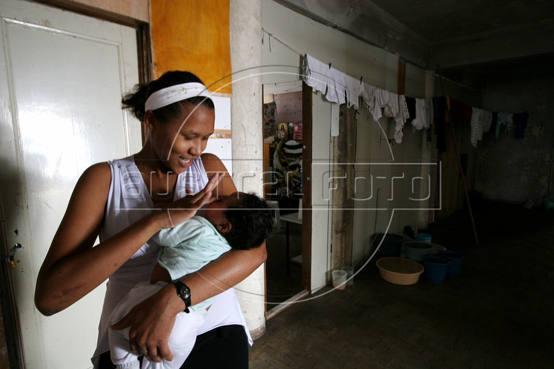 Julienne Cunha holds her two-month old son Newton Rian near her room in an abandoned building in central Sao Paulo, Brazil, Jan. 18, 2006. Julienne is one of thousands of squatting residents of a 22 floor abandoned building commonly referred to as the Prestes Maia occupation, after the avenue it is on in central Sao Paulo.  Julienne is one of the youngest members of the Brazil's sem teto or 'roofless' movement - an urban coalition that is gathering steam in cities across the country. The movement is the urban equivalent to the better-known  MST, Brazil's Movimento dos Sem Terra or Landless Movement which has spearheaded the campaign for land reform since the 1980s. The MST defends Brazil's impoverished rural workers and reclaims unproductive land for the dispossessed. The MSTC reclaims buildings for the homeless and for low income workers, many who work in the informal economy, who just are not able to enter the official housing market.(Australfoto/Douglas Engle)