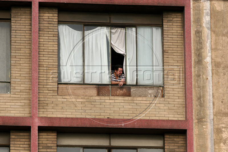 A man looks from the window of an abandoned building in central Sao Paulo, Brazil, Jan. 18, 2006. Thousands are squatting in the 22 floor abandoned building commonly referred to as the Prestes Maia occupation, after the avenue it is on in central Sao Paulo.  The squatters are part of the Brazil's sem teto or 'roofless' movement - an urban coalition that is gathering steam in cities across the country. The movement is the urban equivalent to the better-known  MST, Brazil's Movimento dos Sem Terra or Landless Movement which has spearheaded the campaign for land reform since the 1980s. The MST defends Brazil's impoverished rural workers and reclaims unproductive land for the dispossessed. The MSTC reclaims buildings for the homeless and for low income workers, many who work in the informal economy, who just are not able to enter the official housing market.(Australfoto/Douglas Engle)