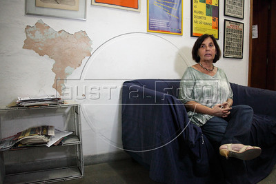 """Vitoria Grabois of the NGO Tortura Nunca Mais (Torture Never Again), next to peeling paint which remarkably resembles the shape of Brazil, at her office in Rio de Janeiro, Brazil. Grabois, who lost her father, brother and husband to the 1964-1985 Brazilian military government says the current Truth Comission proposal is not enough to officially close the dark chapter in the nation's history. Brazil is the only South American nation which has not undergone a reconciliation or judicial process of the dictatorship years. Partly because of this situation, The Inter-American Court of Human Rights ruled in 2010 the """"Brazilian government to publicly accept responsibility for grave human rights violations committed during the military regime, open its archives to the families of victims of repression, and pay millions of dollars in reparations"""" (Australfoto/Douglas Engle)"""