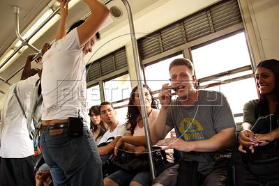 American Alex Cutler, better known as Don Blanquito, makes an impromptu concert on a commuter train to the suburbs, with a vendor's microphone and speaker in Rio de Janeiro, with his girlfriend Yasmin Leiros. After a stint on Wall Street, Blanquito has now emerged as a prominent singer of Carioca funk -- the music of Rio's slums. With a privileged upbringing in L.A., and even has several degrees including an MBA, Cutler  adopted a stage name and threw it all away to chase his dream as a funk performer. His story reflects the shifting dynamics of Rio's favelas, which are home to a growing number of adventurous foreigners, and the evolution of funk music, which some critics say is dying a slow death as life in the favelas gradually improves.(Douglas Engle/Australfoto)