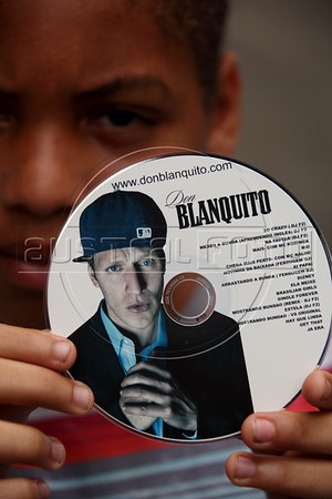 A boy hold up a CD by Alex Cutler, better known as Don Blanquito, who lives in one of Rio de Janeiro's favelas and has emerged as a prominent singer of Carioca funk -- the music of Rio's slums. Alex Cutler had a privileged upbringing in L.A., and even has several degrees including an MBA, then adopted a stage name and threw it all away to chase his dream as a funk performer. His story reflects the shifting dynamics of Rio's favelas, which are home to a growing number of adventurous foreigners, and the evolution of funk music, which some critics say is dying a slow death as life in the favelas gradually improves.(Douglas Engle/Australfoto)