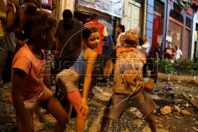 Children dance to the Carioca Funk beat outside a club in Rio de Janeiro where American Alex Cutler, better known as Don Blanquito, has a performance. After a stint on Wall Street, Blanquito has now emerged as a prominent singer of Carioca funk -- the music of Rio's slums. With a privileged upbringing in L.A., and even has several degrees including an MBA, Cutler  adopted a stage name and threw it all away to chase his dream as a funk performer. His story reflects the shifting dynamics of Rio's favelas, which are home to a growing number of adventurous foreigners, and the evolution of funk music, which some critics say is dying a slow death as life in the favelas gradually improves.(Douglas Engle/Australfoto)