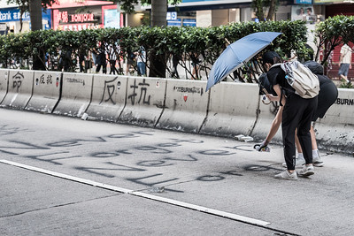 "Protesters spray ""Never Forget"" on Nathan Road during an anti-government protest in Hong Kong. October 20, 2019."