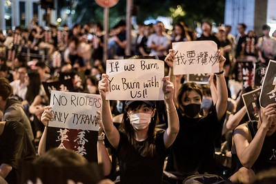 Protesters gathered near Chater Garden in Hong Kong hold up protest signs. August 16, 2019.