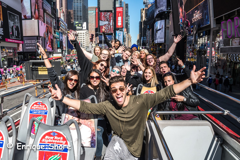 American pop singer Jake Miller and fans pose atop a bus in New York's Times Square