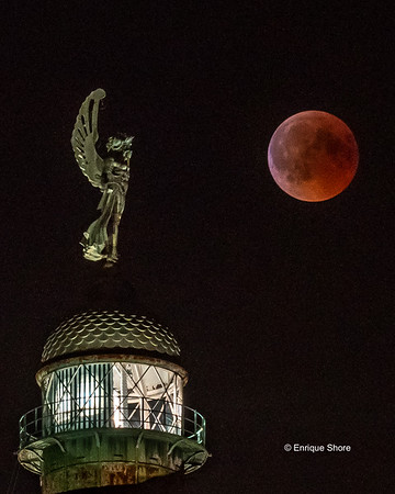 Moon eclipse and Vittoria lighthouse in Trieste, Italy