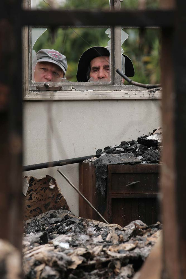 Roger Jacobson, left, and his father-in-law Robert Pratini peer into the bedroom of Pratini's burned home in Santa Barbara, Calif., on Sunday, May 10, 2009, after it was destroyed in the Jesusita wildfire.   Pratini and his wife were among thousands of evacuees who fled their homes when high winds drove the blaze out of control and into neighborhoods last week.  (AP Photo by Eric Parsons)