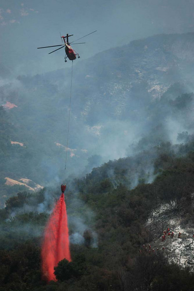 With a hand crew of trustees working nearby, at right, a firefighting helicopter drops a load of fire retardant in Santa Barbara, Calif., along San Marcos Pass Road to help bolster the western edge of the containment line around the Jesusita wildfire on Saturday, May 9, 2009.  Cooler, more humid weather and a decrease in winds gave firefighters a chance to gain some ground against the fire which has consumed more than 8,000 acres and destroyed at least 80 homes.  (AP Photo by Eric Parsons)