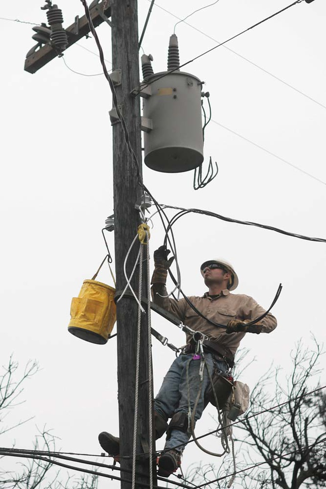 Southern California Edison Apprentice Lineman Daniel Montiel worked to replace damaged power lines and transformers along Tunnel Road on Monday, May 11, 2009 in Santa Barbara, Calif.  The area was devastated by the Jesusita wildfire, leaving may homes without electricity.  (AP Photo by Eric Parsons)