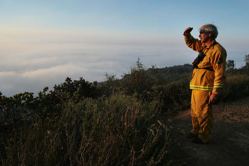 Cal Fire Battalion Chief Craig Konklin surveys his division in the San Marcos Pass from a vantage point along Painted Cave Road in Santa Barbara, Calif., as a thick marine layer mixes with smoke from the Jesusita wildfire early on Saturday, May 9, 2009.  (AP Photo by Eric Parsons)