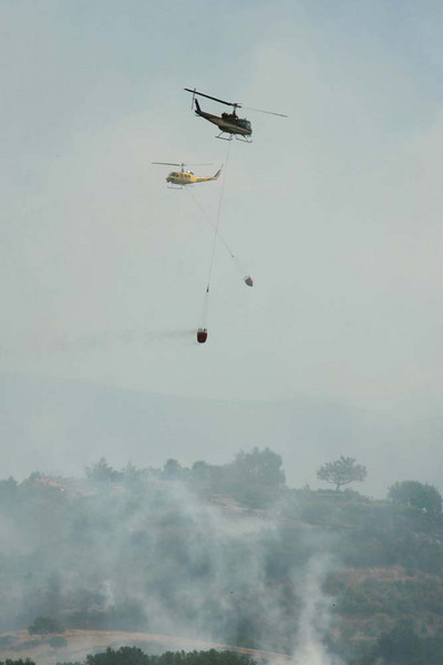 Firefighting helicopters take turns dropping water on spot fires threatening homes in Santa Barbara, Calif., along San Marcos Pass Road on Friday morning, May 8, 2009.  The Jesusita wildfire jumped its western flank, sending flames across Highway 154 in the early morning hours and causing the evacuation of thousands of residents.  (AP Photo by Eric Parsons)