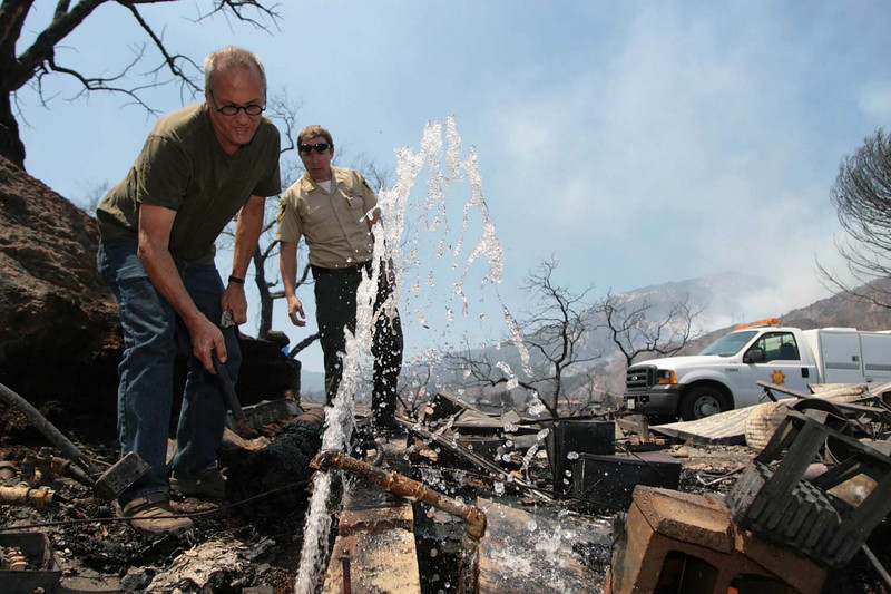 Robert Miller, left, and Santa Barbara County Public Health Department Animal Services officer Malcolm Cross attempt to shut off the water supply to a home on Thursday, May 7, 2009, that was burned to the ground by the Jesusita wildfire along Tunnel Road.  The spewing water threatened to erode the hillside above Miller's nearby home, which survived the fire.   (AP Photo by Eric Parsons)