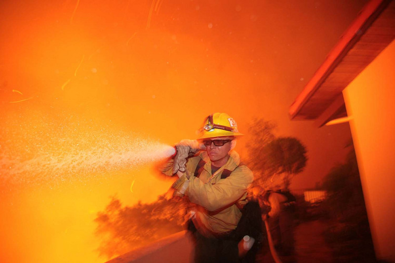 U.S. Forest Service firefighter Josh Langston runs to douse flames as he helps protect a home from from advancing fire along Northridge Road Santa Barbara, Calif., during the Jesusita wildfire in the evening on Thursday, May 7, 2009.  Wild winds blew flame and embers through the air as firemen braved the unchecked blaze.  (AP Photo by Eric Parsons)