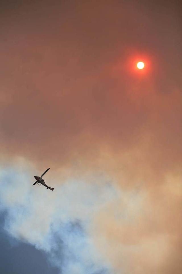 A spotter helicopter checks out hot spots threatening homes in Santa Barbara, Calif., along San Marcos Pass Road as the battle against the Jesusita wildfire continues on Friday, May 8, 2009.  (AP Photo by Eric Parsons)