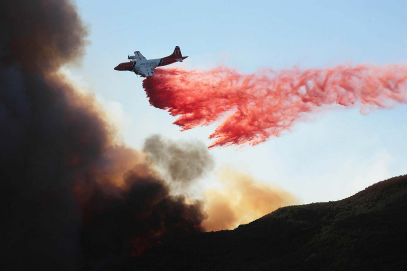 A firefighting aircraft drops fire retardant material along a ridgeline at edge of Rattlesnake Canyon above Santa Barbara, Calif., as the battle against the Jesusita wildfire continues on Thursday, May 7, 2009.  Fire officials are worried that if the fire makes its way in to the canyon, more homes would be threatened.  (AP Photo by Eric Parsons)