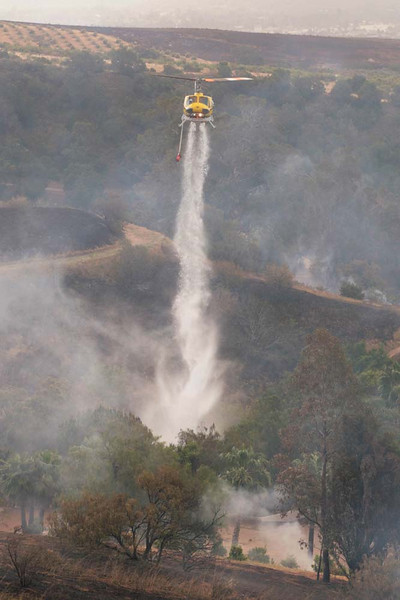 A firefighting helicopter douses a spot fire in Santa Barbara, Calif., along San Marcos Pass Road as the battle against the Jesusita wildfire continues on Friday, May 8, 2009.  The fire overran its western flank overnight, starting spot fires dangerously close to homes.  (AP Photo by Eric Parsons)