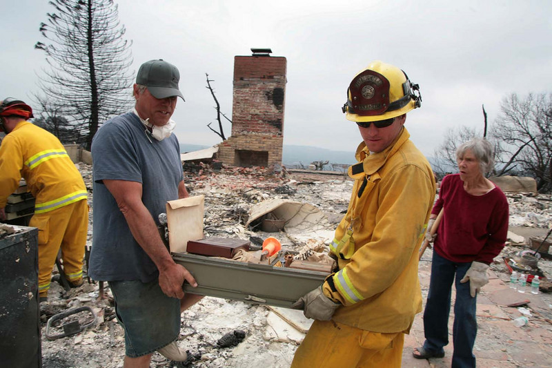 Dennis Pike, left, carries a drawer full of valuables with the help of Anaheim Fire Department firefighter Ryan Herr from his mother's home along Tunnel Road on Monday, May 11, 2009, which was destroyed by the Jesusita wildfire in Santa Barbara, Calif.  Pike grew up in the home, which also burned to the ground during another wildfire in 1964.  (AP Photo by Eric Parsons)