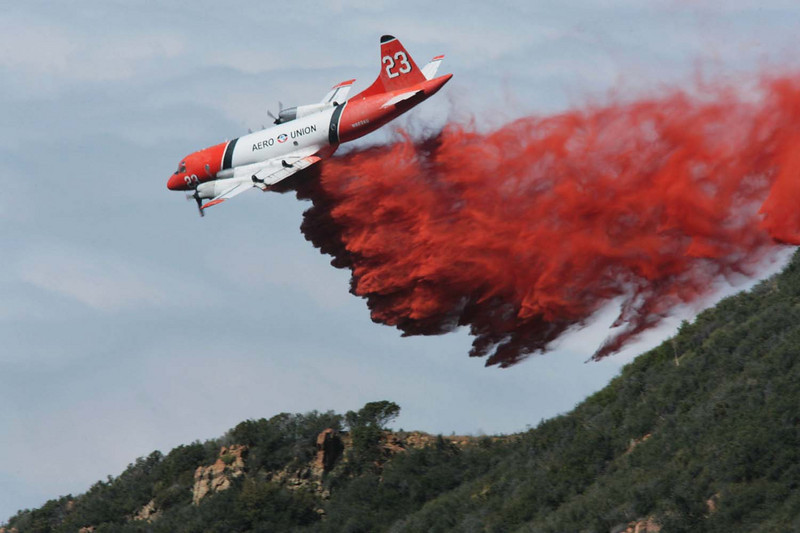 Against the backdrop of a thick marine layer over the Pacific Ocean, a firefighting P-3 aircraft drops a line of fire retardant along a sloping dozer line in the mountains high above Santa Barbara, Calif., where fire crews worked to complete a containment barrier around the western flank of the Jesusita wildfire on Saturday, May 9, 2009.  (AP Photo by Eric Parsons)