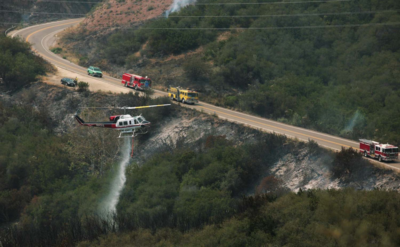A firefighting helicopter douses a spot fire beside San Marcos Pass Road in Santa Barbara, Calif., as the battle against the Jesusita wildfire continues on Friday, May 8, 2009.  Fire crews worked hard during the day to extinguish spot fires in anticipation of sundowner winds that were predicted for the late afternoon and evening hours.  (AP Photo by Eric Parsons)