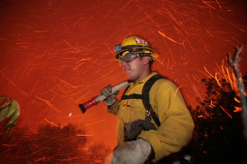 U.S. Forest Service firefighter Mike Espinoza is overcome by flying embers as erratic winds blow the Jesusita wildfire towards homes along Northridge Road in Santa Barbara, Calif., on Thursday, May 7, 2009.  (AP Photo by Eric Parsons)