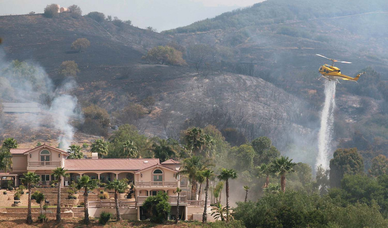 A firefighting helicopter douses a spot fire threatening a home in Santa Barbara, Calif., along San Marcos Pass Road as the battle against the Jesusita wildfire continues on Friday, May 8, 2009.  (AP Photo by Eric Parsons)