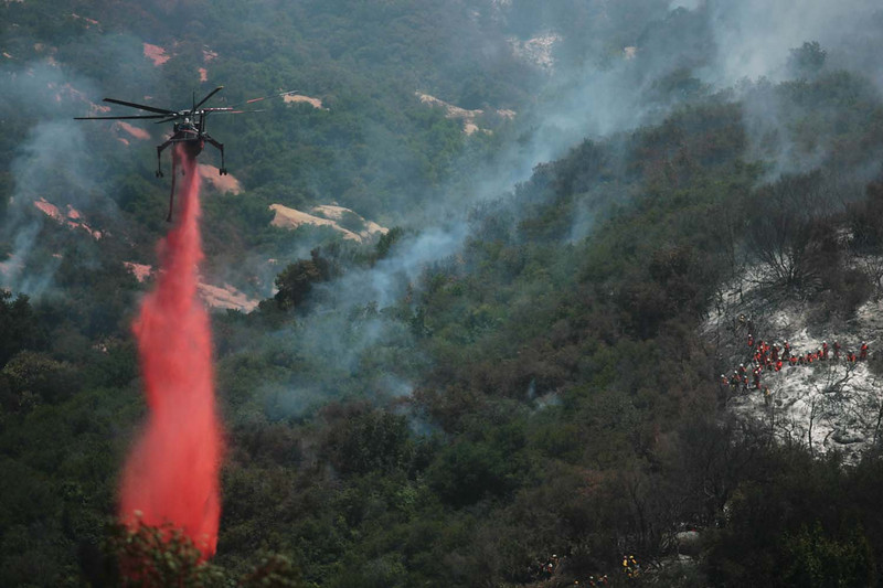 With a hand crew of trustees working at right, a firefighting helicopter drops a load of fire retardant on smoldering hot spots in Santa Barbara, Calif., along San Marcos Pass Road in an effort to bolster the western flank of the Jesusita wildfire on Saturday, May 9, 2009.  (AP Photo by Eric Parsons)