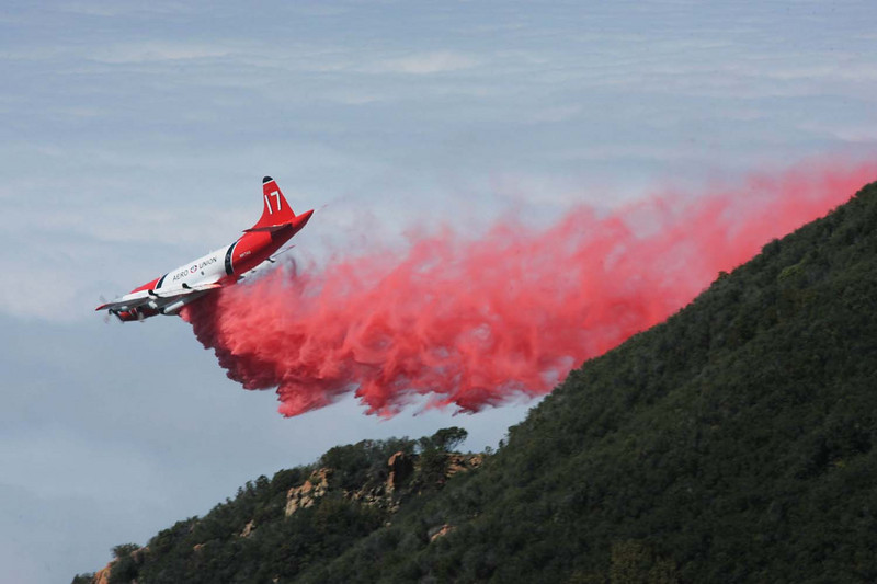 Against the backdrop of a thick marine layer over the Pacific Ocean, a firefighting C-130 aircraft drops a line of fire retardant along a sloping dozer line in the mountains high above Santa Barbara, Calif., where fire crews worked to complete a containment barrier around the western flank of the Jesusita wildfire on Saturday, May 9, 2009.  (AP Photo by Eric Parsons)