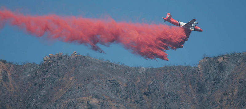 A firefighting aircraft drops fire-retardant material along a ridgeline above Santa Barbara, Calif., as the battle against the Jesusita wildfire continues on Thursday, May 7, 2009.  (AP Photo by Eric Parsons)