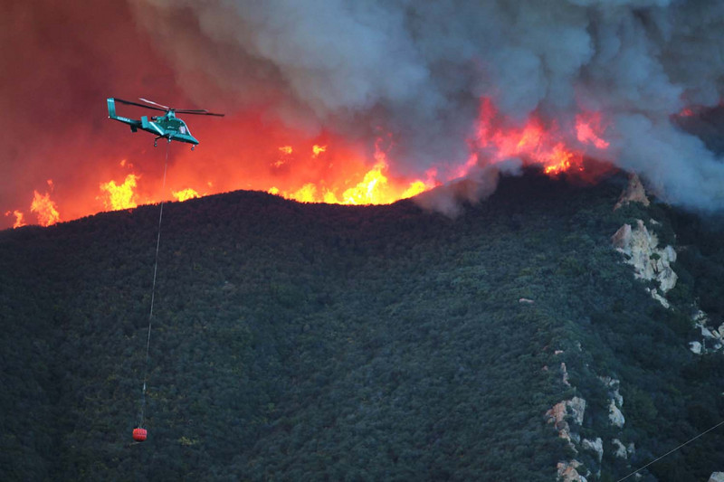 A firefighting helicopter makes a water drop along a ridgeline above Rattlesnake Canyon in Santa Barbara, Calif., as the battle against the Jesusita wildfire continues on Thursday, May 7, 2009.  (AP Photo by Eric Parsons)
