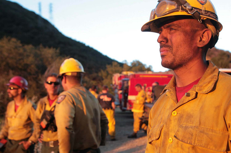 Vandenburg Hot Shots crew member Joel Rodriguez finally got to take a break after working all day to cut firelines in Rattlesnake Canyon in Santa Barbara, Calif., as the Jesusita wildfire advanced on Thursday, May 7, 2009.  (AP Photo by Eric Parsons)