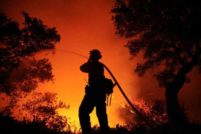 U.S. Forest Service firefighter Josh Langston keeps flames in check near a home along Northridge Road in Santa Barbara, Calif., on Thursday, May 7, 2009 as he and other firemen battled the Jesusita wildfire.  (AP Photo by Eric Parsons)
