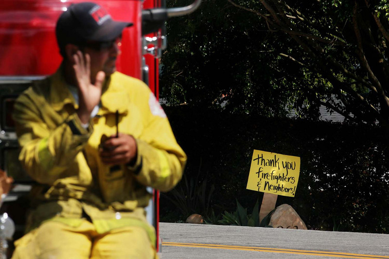 Santa Ana Fire Department firefighter Robert Smith returns a greeting to a grateful resident along Cheltenham Road in Mission Canyon on Sunday, May 10, 2009, where Smith and thousands of other firemen have been working for several days to protect homes threatened by the Jesusita wildfire in Santa Barbara, Calif.  Although Smith and his fellow firemen from Santa Ana had been working in more volatile conditions over the past few days, Sunday brought the task of facilitating residents returning home after evacuations and keeping an eye out for hot spots.  (AP Photo by Eric Parsons)