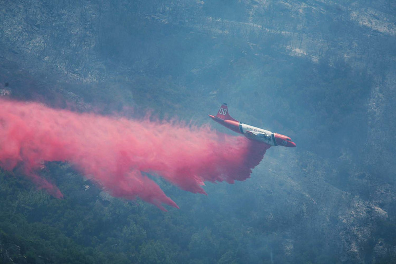 An air tanker dumps retardant material on smoldering hot spots along San Marcos Pass Road in Santa Barbara, Calif., as the fight against the Jesusita wildfire continues on Saturday, May 9, 2009.  Air assets were used extensively throughout the day to reinforce a containment line around the blaze while there was a break in the hot, windy weather.  (AP Photo by Eric Parsons)