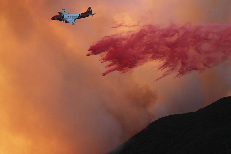 With a drop of fire retardant material along a ridgeline, a firefighting aircraft attempts to keep the Jesusita wildfire from crossing over into Rattlesnake Canyon in Santa Barbara, Calif., as the battle against the blaze continues on Thursday, May 7, 2009.  (AP Photo by Eric Parsons)