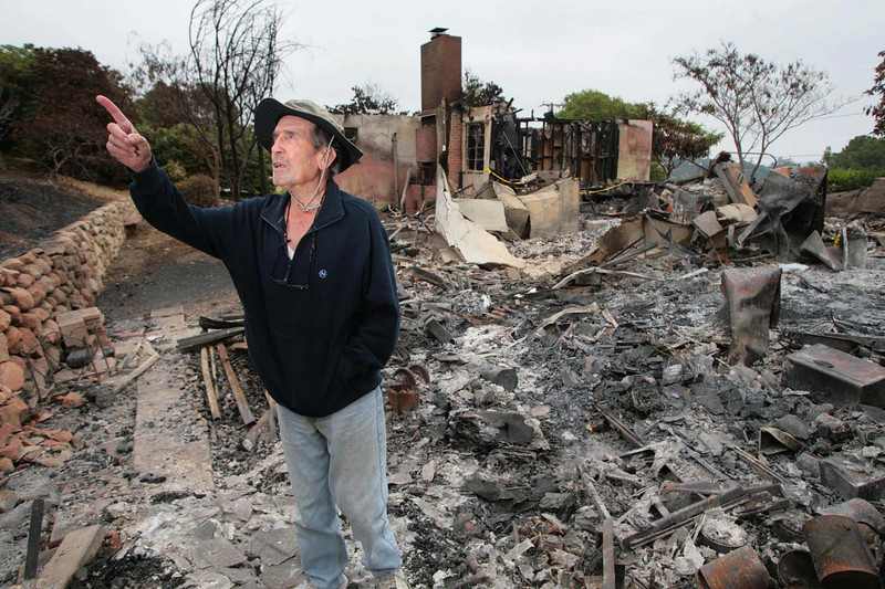 "Robert Pratini, 88, surveys the destruction on Sunday, May 10, 2009, as he realizes his avacado trees had burned in the Jesusita fire that also claimed his home in Santa Barbara, Calif., on Sunday, May 10, 2009.  A veteran of several wildfires over the years, Pratini said he and his wife refused evacuation orders when authorities warned them of the fire. ""I've been through it more than they have,"" he said of law enforcement officers. But when high winds blew the fire out of control and toward his home, Pratini changed his mind.  (AP Photo by Eric Parsons)"