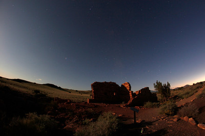 Rising moon to the left, setting sun to the right, faint Milky Way in the middle.