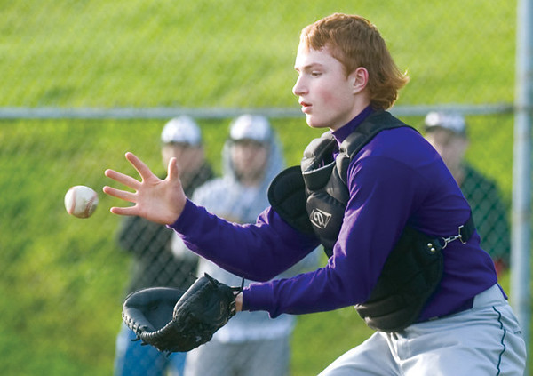 ALEX PAJUNAS — The Daily Astorian<br /> Astoria's Cooper Wullger fields a throw from the outfield at home plate.