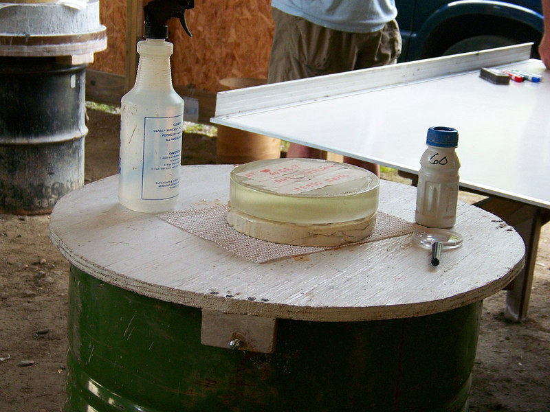 "A close up of the more traditional setup for making telescope mirrors. Here a plywood top is afixed to a 55 gallon steel drum filled 3/4 of the way with water. The Pyrex mirror can now be ground on top of a disk made of plaster and cermaic tiles called ""the tool"". # 60 grit and a bottle of water shown is the grinding medium. The mirror and tool sit upon a cloth that is dampened, and will stay put while the he two disks are rubbed together by hand."