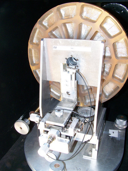 "Another close-up of a portion of the ""ingredients"" to test optics. This Foucault Tester resides in front of a precision 12.5 inch optical flat. The tester throws out light to the telescope mirror being tested at the other end of the optical tunnel. The light comes back from the mirror being tested to hit  the big 12.5 inch optical flat mirror. The flat mirror then reflects the cone of light back to the primary mirror being tested and the return beam comes back to us by passing thru a hole in the back of the big optical flat. Since the light cone makes a double pass it is often called a ""DOUBLE PASS TEST"". Using a set up in this manor is rewarding because it is twice as accurate as the standard Foucault test methods, due to the double pass, and the light effectively ""nulls"" out the light cone. Meaning the zones really don't have to measured when using this apparatus. What we are really looking for virtually NO longitudal  movement, as measured at the Foucault testing device. When this is experienced we have finished our telescope mirror!"