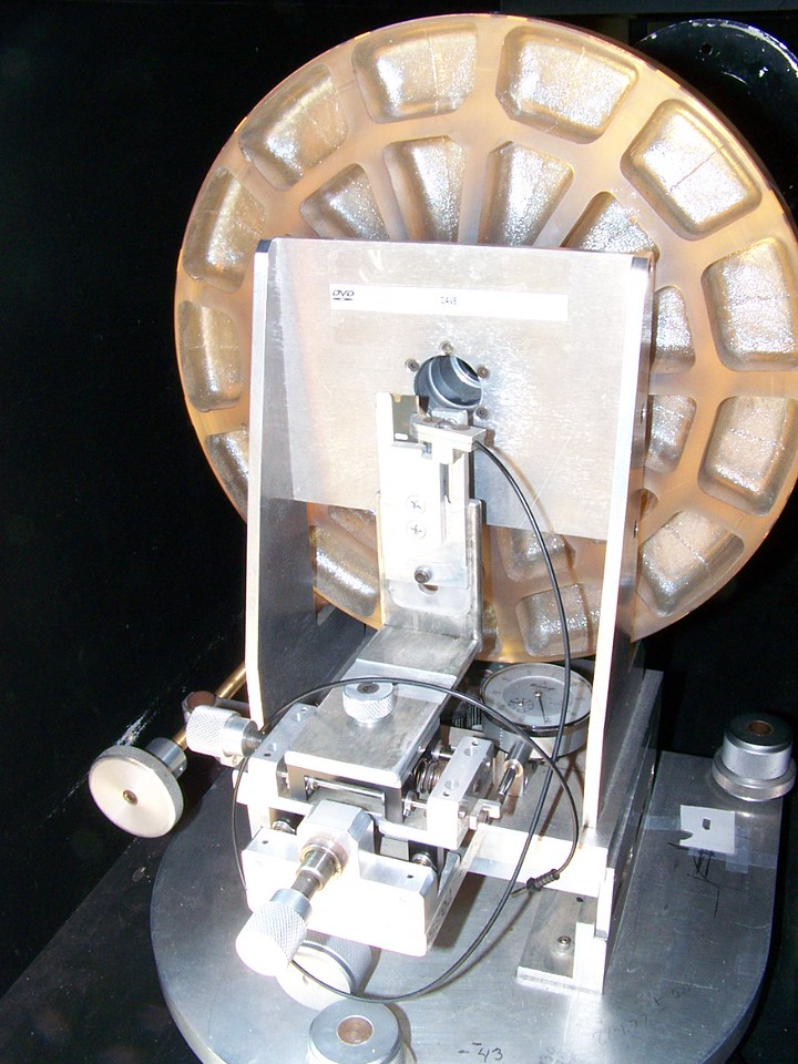 """Another close-up of a portion of the """"ingredients"""" to test optics. This Foucault Tester resides in front of a precision 12.5 inch optical flat. The tester throws out light to the telescope mirror being tested at the other end of the optical tunnel. The light comes back from the mirror being tested to hit  the big 12.5 inch optical flat mirror. The flat mirror then reflects the cone of light back to the primary mirror being tested and the return beam comes back to us by passing thru a hole in the back of the big optical flat. Since the light cone makes a double pass it is often called a """"DOUBLE PASS TEST"""". Using a set up in this manor is rewarding because it is twice as accurate as the standard Foucault test methods, due to the double pass, and the light effectively """"nulls"""" out the light cone. Meaning the zones really don't have to measured when using this apparatus. What we are really looking for virtually NO longitudal  movement, as measured at the Foucault testing device. When this is experienced we have finished our telescope mirror!"""